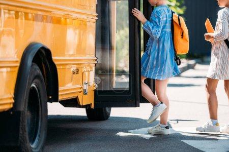 cropped shot of schoolgirls entering school bus