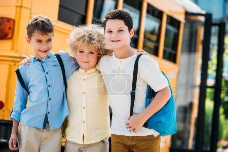 Foto de Adorables colegiales poco abrazar frente a autobús de la escuela y mirando a cámara - Imagen libre de derechos