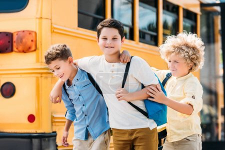 adorable little schoolboys having fun together in front of school bus