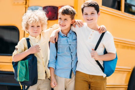 adorable little schoolboys embracing in front of school bus