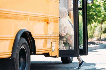 little schoolboys running into school bus