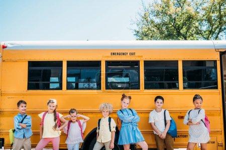 group of happy scholars posing in front of school bus
