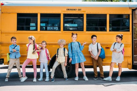 group of happy pupils posing in front of school bus
