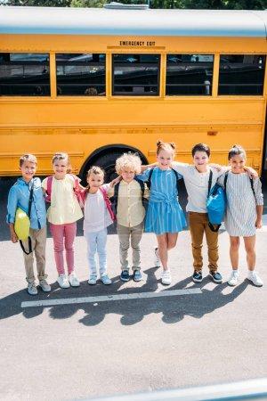Foto de Grupo de escolares felices de pie frente al autobús escolar y mirando a la cámara - Imagen libre de derechos