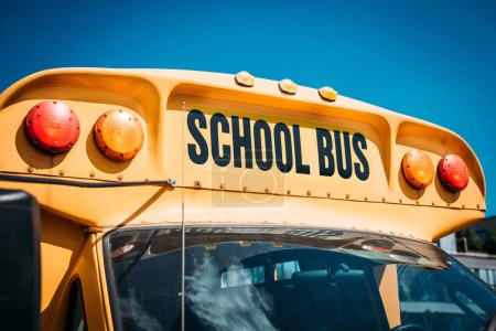 close-up shot of school bus with sign in front of blue sky