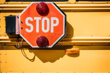 cropped shot of school bus with stop sign