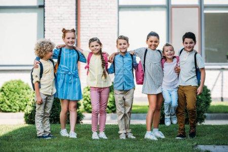 Foto de Grupo de escolares adorables de pie en el jardín de la escuela y mirando a la cámara - Imagen libre de derechos
