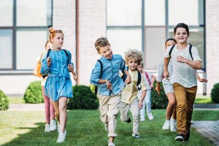 group of happy pupils runing by school garden