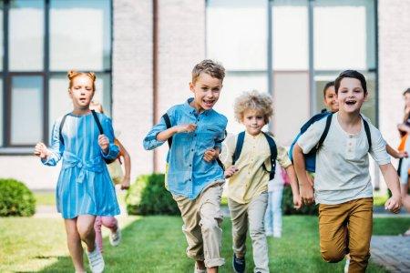 group of adorable scholars runing by school garden