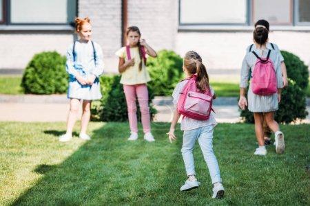 Vista posterior de los alumnos con bakpacks waling por jardín de la escuela