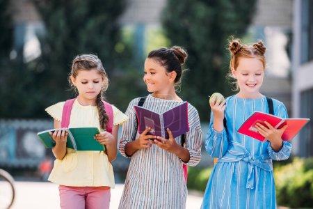 Photo pour Heureux écolières avec cahiers passer du temps ensemble après l'école - image libre de droit