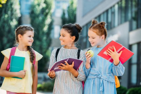 group of happy schoolgirls with notebooks spending time together after school