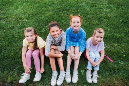 Photo for High angle view of group of happy schoolgirls sitting on green grass together and looking at camera - Royalty Free Image