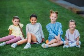 group of happy schoolgirls sitting on green grass together and looking at camera
