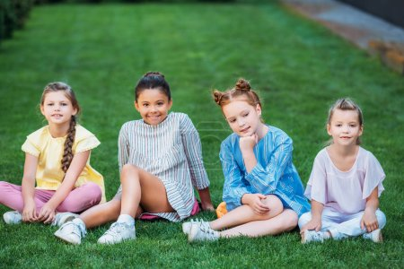 group of adorable schoolgirls sitting on green grass together and looking at camera