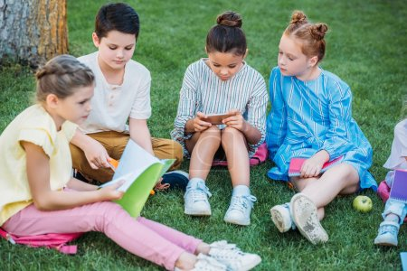 group of adorable pupils spending time together on grass after school