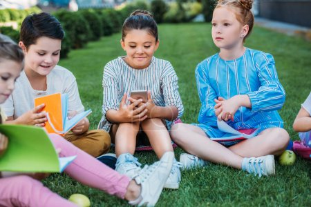 group of adorable schoolchildren spending time together on grass after school