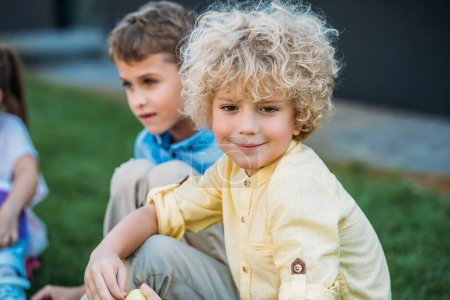 adorable curly schoolboy sitting on grass with classmate