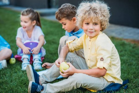 adorable curly schoolboy with apple sitting on grass with classmates