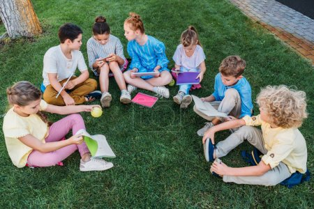 high angle view of group of adorable schoolchildren sitting on grass with books and devices
