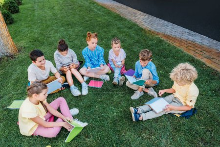 high angle view of group of pupils sitting on grass with books and devices
