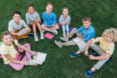 high angle view of group of happy schoolchildren sitting on grass with books and devices
