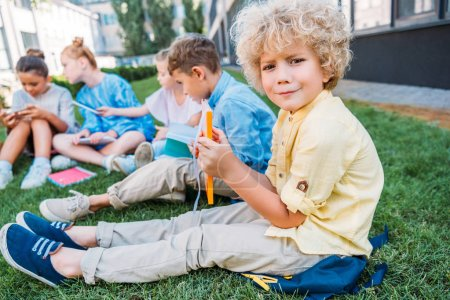 confused curly schoolboy holding book while sitting on grass with classmates