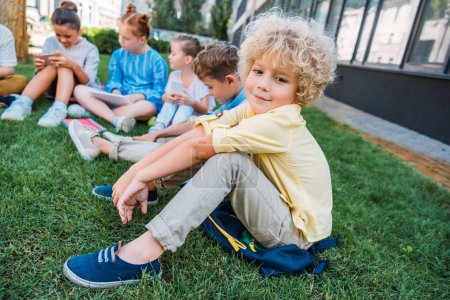 Photo for Adorable curly schoolboy sitting on grass with classmates - Royalty Free Image