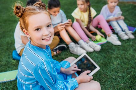 smiling adorable schoolgirl using tablet while sitting on grass with classmates
