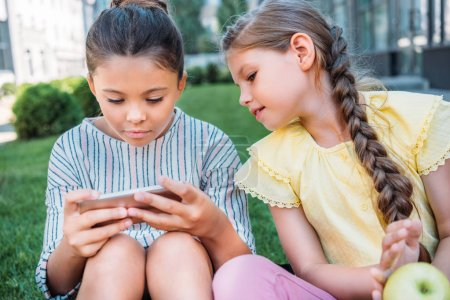adorable little schoolgirls using smartphone together