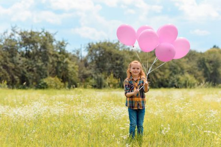 smiling child with pink balloons standing in summer field