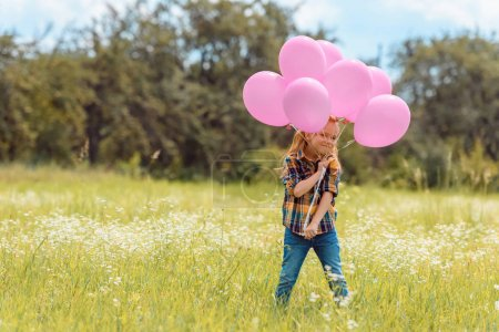 adorable child with pink balloons standing in summer field