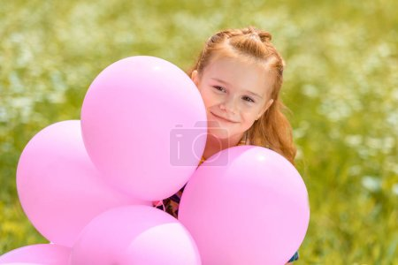 portrait of smiling adorable child with pink balloons in summer field