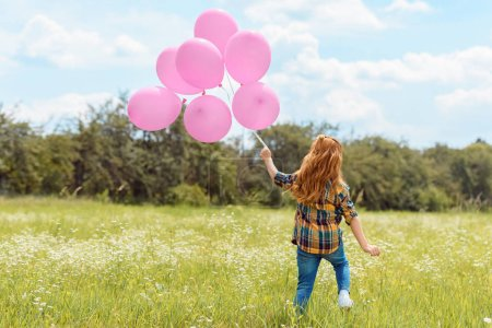 back view of child with pink balloons standing in summer field with blue sky on background
