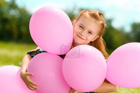portrait of smiling cute child hugging pink balloons in summer field