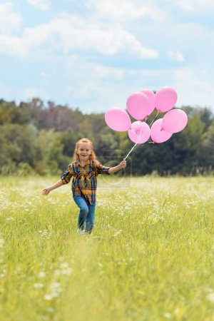 cheerful kid with pink balloons in hand running in meadow
