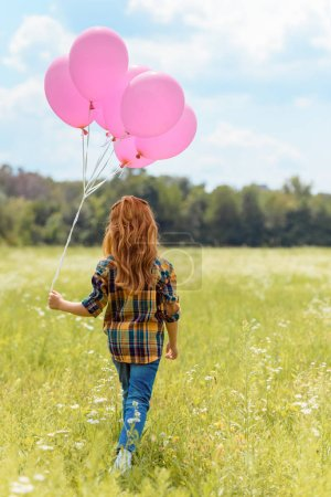 back view of child with pink balloons walking in summer field