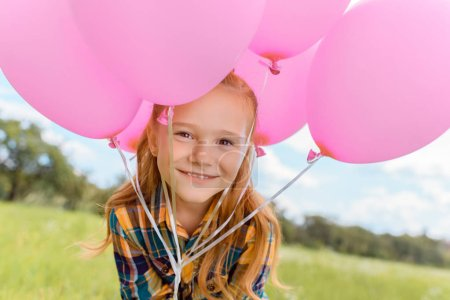 portrait of cute child with pink balloons looking at camera in summer field