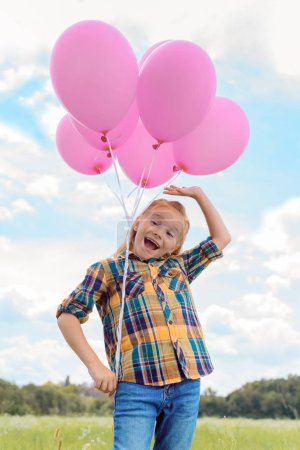 low angle view of cute child with pink balloons in summer field with blue cloudy sky on background
