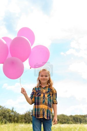 portrait of cute child with pink balloons in summer field with blue cloudy sky on background