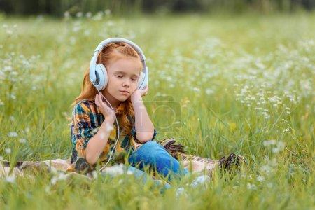 petit enfant avec les yeux fermés musique écoute au casque tout en reposant sur la couverture en pré