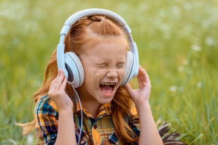 portrait of kid screaming while listening music in headphones with green grass on background