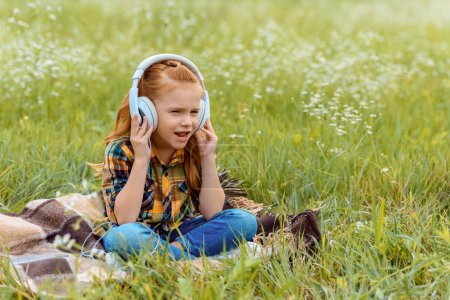 cute kid listening music in headphone while sitting on blanket in field with wild flowers