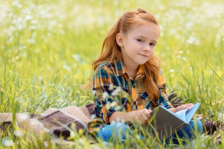 Photo for Portrait of adorable red hair child with book sitting in summer field - Royalty Free Image