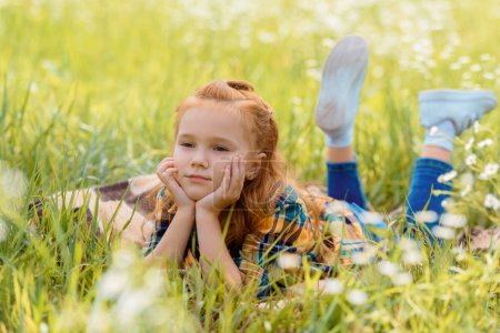 portrait of little pensive child resting on green grass in meadow
