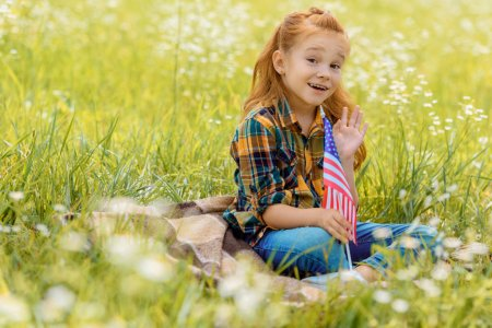 emotional kid with american flagpole resting on green grass in field