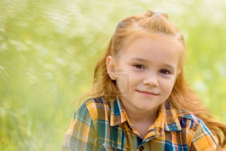 Photo for Portrait of adorable kid looking at camera with blurred green grass on background - Royalty Free Image