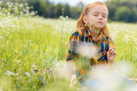 portrait of kid with eyes closed and wild flowers in hand resting in meadow