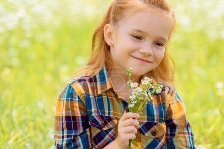 Foto de Retrato de sonriente niño con ramo de flores silvestres en mano - Imagen libre de derechos