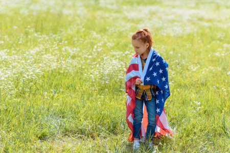 Photo for Red hair child covered in american flag standing in summer field - Royalty Free Image
